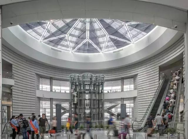 我们创造了一个圆形中庭,让所有换乘旅客都经过这里,中庭的四周相对